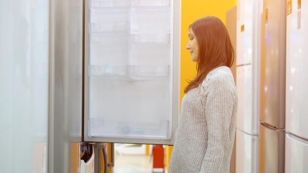 Магазин бытовой техники. молодая женщина выбирает холодильник.