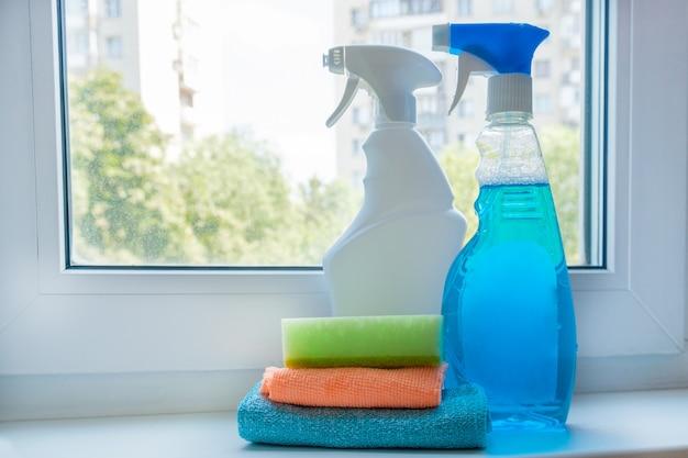 汚れた窓の背景にある窓辺の窓を掃除するためのスプレーボトルの家庭用化学薬品
