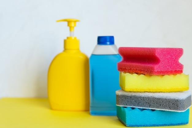 Бытовая химия на белом фоне. профессиональные чистящие средства, весенняя уборка. желтые и синие пластиковые контейнеры для бытовых моющих средств, бытовой химии. моющие средства.
