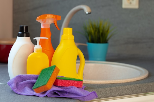 Household chemicals product bottles standing near the kitchen sink