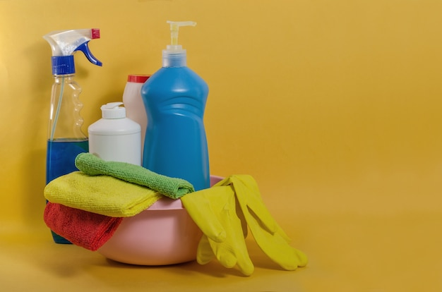 Household cleaning products with colorful napkins on a yellow space