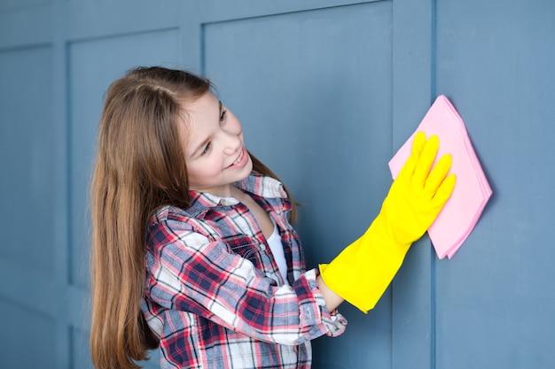 家事と子供の助け。家の壁を掃除する少女。
