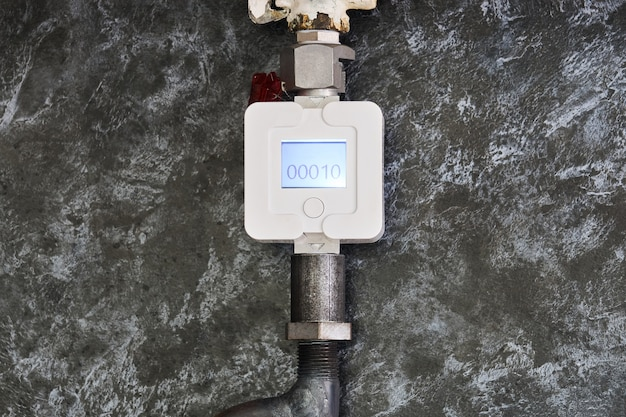 Household gas meter is installed on a pipe in the kitchen against the background of a decorative panel
