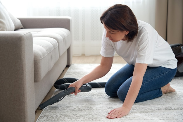 Household and housework concept - happy woman or housewife with vacuum cleaner cleaning floor under couch at home