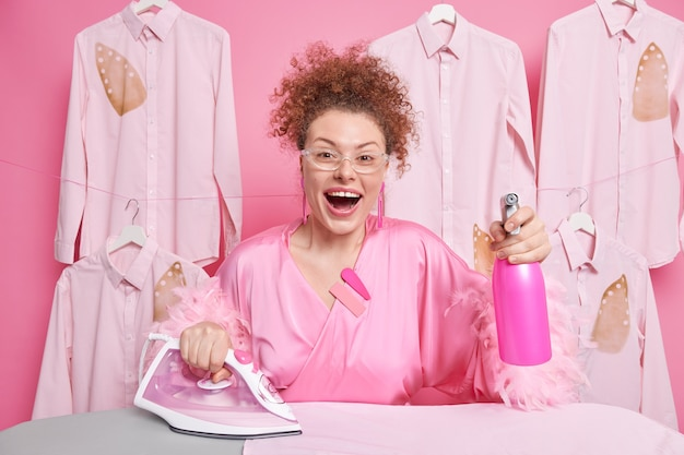 Household ironing concept. positive curly haired young woman dressed in domestic robe holds water spray anduses electric iron wears transparent goggles has cheerful expression does daily chores