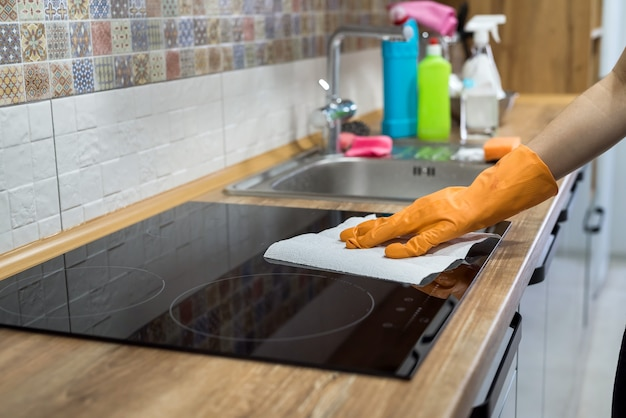 Housekeeper cleaning modern ceramic stove surface with a sponge in the kitchen