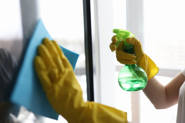 Housekeeper in gloves washing window with napkin closeup