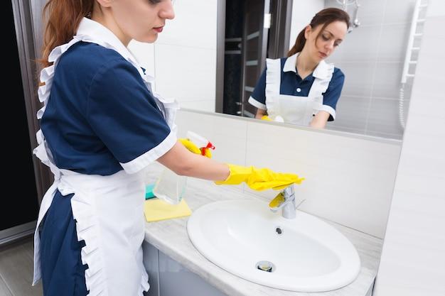 鏡に映った黄色い布で洗面台と蛇口を洗ったり掃除したりするホテルのバスルームにサービスを提供するきちんとした制服とエプロンの家政婦