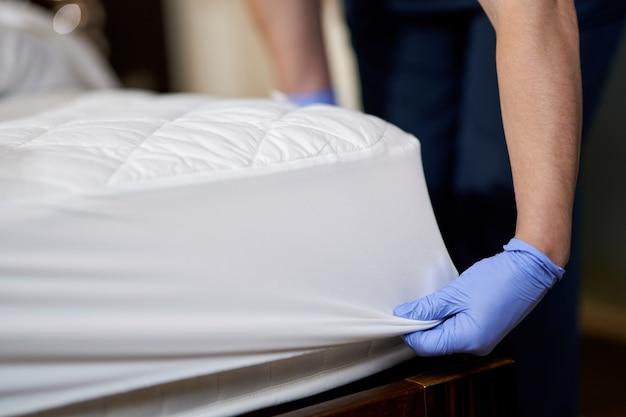 Домработница в перчатках меняет постельное белье в гостиничном номере