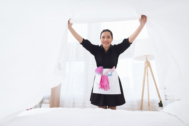 Housekeeper sets up white clean bedding sheets.