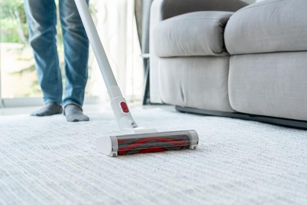 Домработница с помощью беспроводного пылесоса чистит ковер в гостиной дома. закрыть вверх