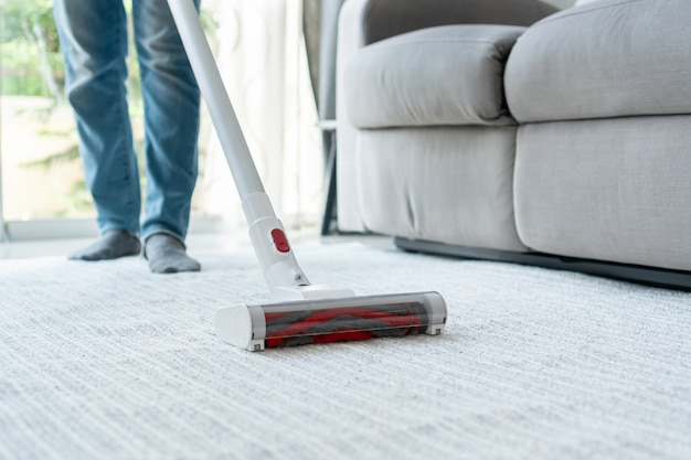 Housekeeper using wireless vacuum cleaner cleaning carpet in living room at home. close up