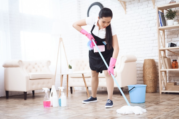 Housekeeper wiping floor with mop and detergents.