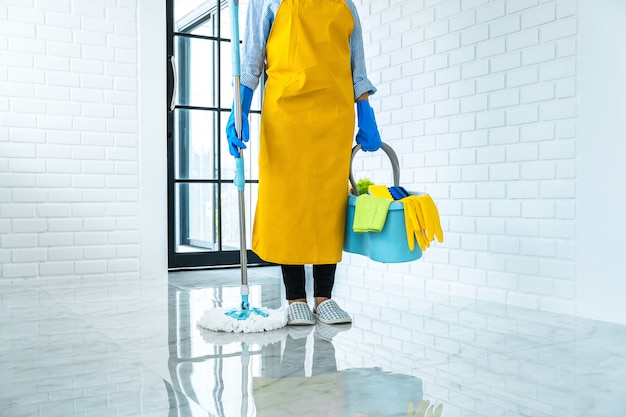 Housekeeping and cleaning concept, happy young woman in blue rubber gloves wiping dust using mop while cleaning on floor at home