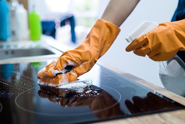 彼女の台所の家事でスポンジで現代のガラスセラミック電気表面を掃除するハウスキーピング