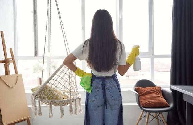 Housekeeping and cleaning service concept back view of a young woman cleaning lady in yellow