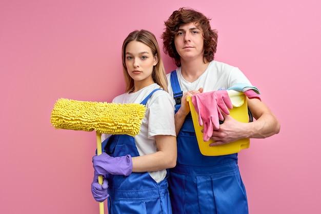가사 개념. 손에 청소 용품을 가진 자신감있는 남편과 아내가 집에서 청소를 시작합니다.