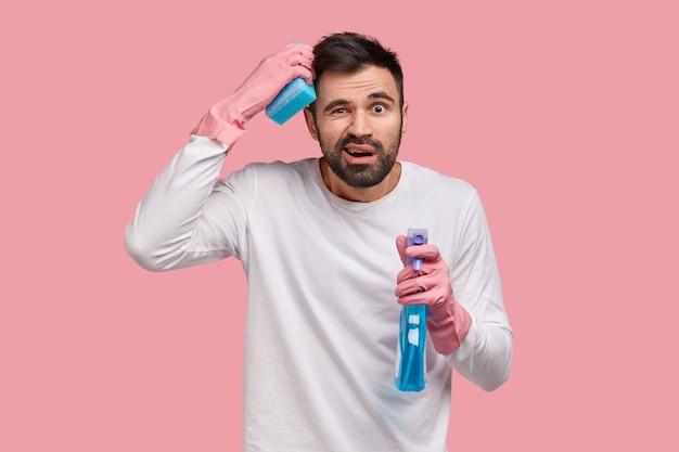 Концепция домашнего хозяйства. расстроенный бородатый молодой парень в замешательстве чешет затылок, у него расстроенное выражение лица, он носит повседневный белый свитер