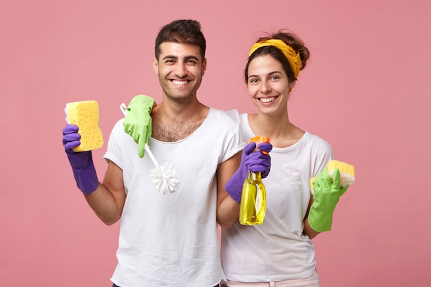 Housekeeping, domestic duties and teamwork concept. beautiful young european family sharing household chores: woman with sponge and toilet brush cleaning bathroom while man washing windows with spray