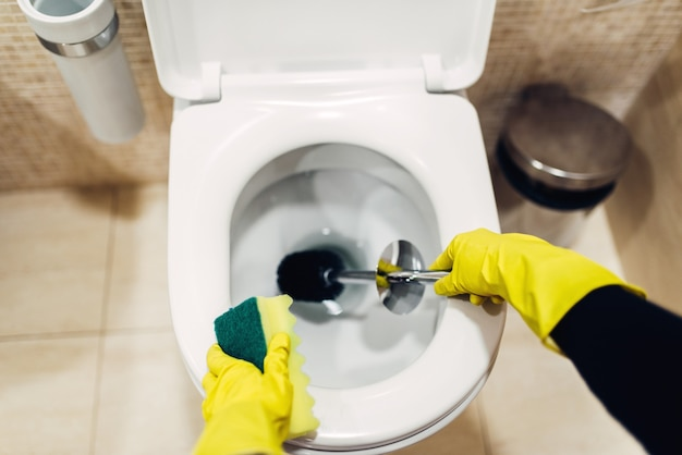 Housemaid hands in rubber gloves cleans the toilet with brush, hotel restroom interior. professional housekeeping service, charwoman, sanitary processing