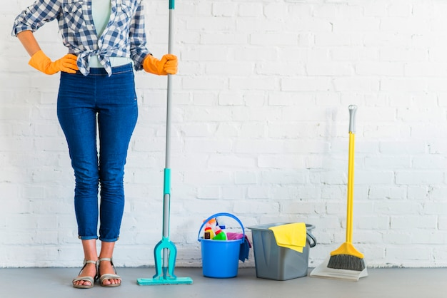 Housemaid holding mop near cleaning equipments in front of brick wall