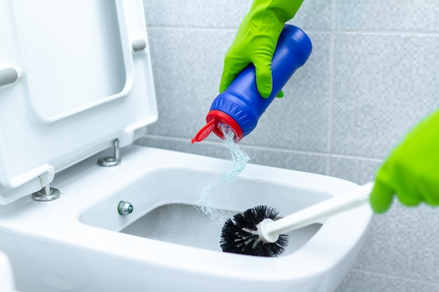 Домработница в резиновых перчатках моет и дезинфицирует унитаз с помощью чистящих средств и щетки. работа по дому и уборка
