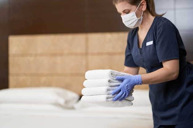 Горничная готовит чистые полотенца в убранной комнате