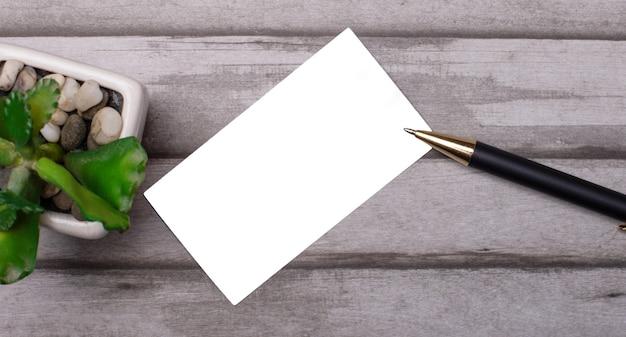 観葉植物、ペン、木製の背景のテキストの空白の白いカード。コピースペース