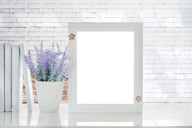 白いテーブルと白いレンガの壁の上に空のページとhouseplantと木製フレームをモックアップ