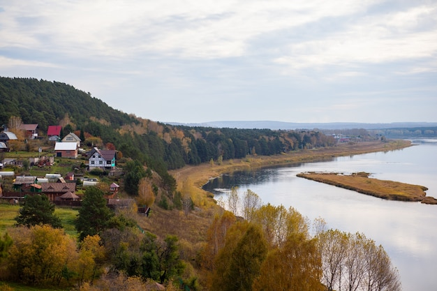 Houses along a beautiful, wide river in the middle of the forest. calm and quiet place with autumn colors. in the middle of the river island. view from the top to the distance