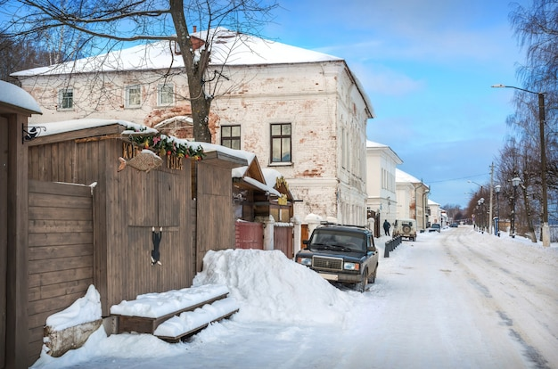 Дома и рыбный магазин на набережной волги в плёсе в свете зимнего дня