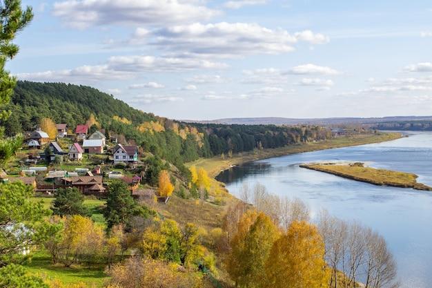 Дома у красивой широкой реки посреди леса в тихом и спокойном месте