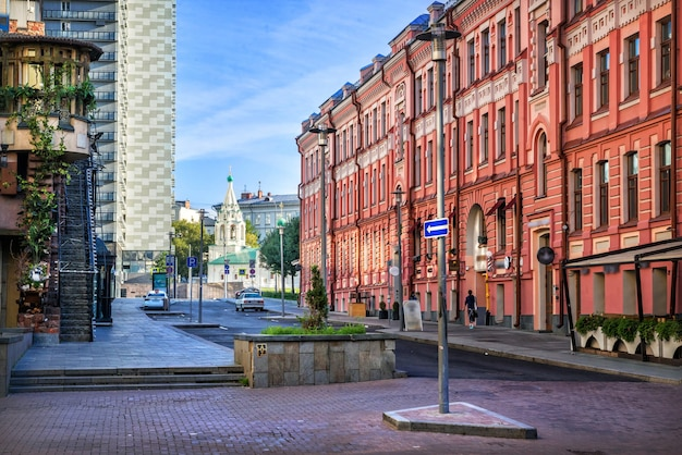 Houses and cafes and a church in a lane on arbat in moscow on a summer morning