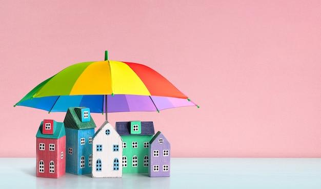 무지개색 우산으로 덮인 집들. 보호, 부동산, 재산 개념의 보험 보안.