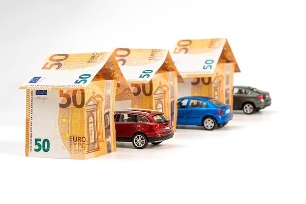 白で隔離されたユーロ紙幣と車両からの家。ローン、不動産、自動車保険のコンセプト