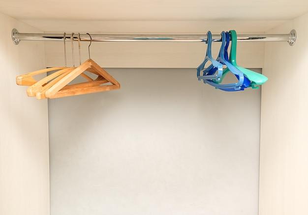 Дома пластиковые и деревянные вешалки висят в новом пустом шкафу. вешалки для одежды.