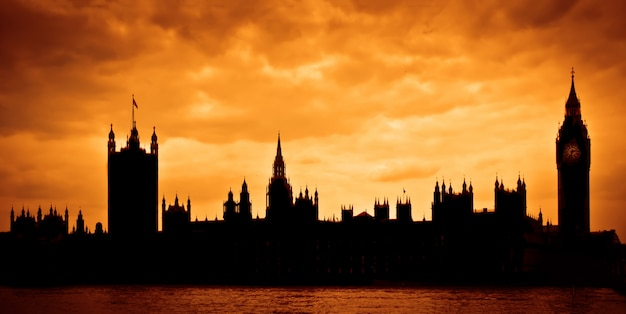Houses of parliament at sunset, silhouette over dramatic sky