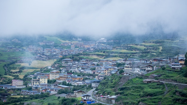 Houses of a small town surrounded by forests and a foggy cloud