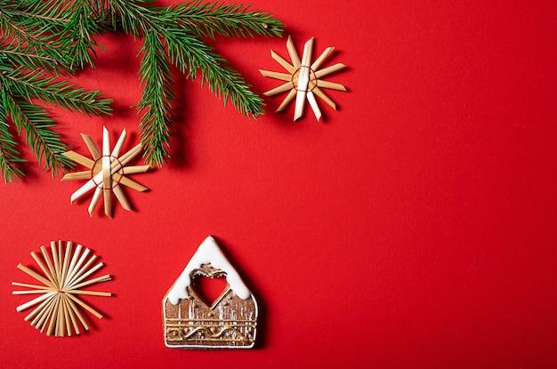 Дома-украшения для печенья и еловые ветки на красном фоне