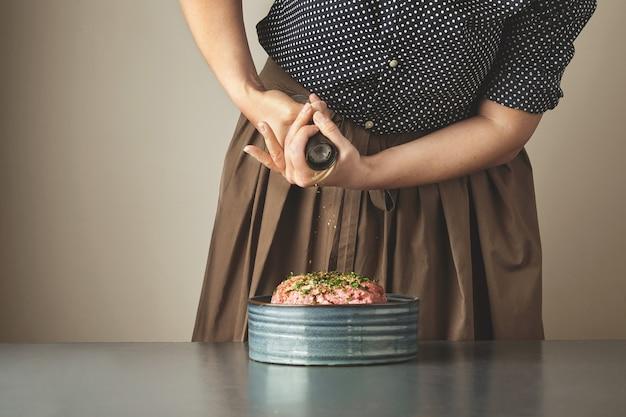 주부는 파란색 테이블에 세라믹 그릇에 다진 고기에 후추 향신료를 추가합니다.