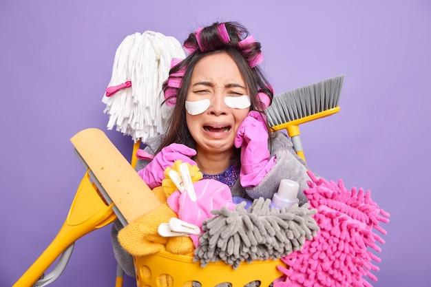 Casalinga applica bigodini per acconciature indossa cerotti sotto gli occhi si sottopone a procedure di bellezza mentre fa i lavori di casa circondata da attrezzi per la pulizia fa il bucato