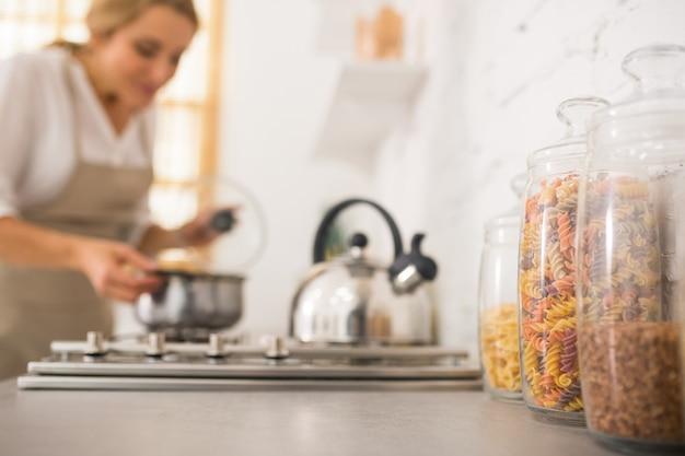 Housewife in apron stirring something in a sausepan