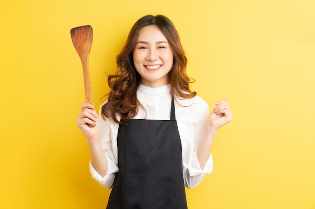 Housewife beauty holding rice spoon and smile isolated on yellow