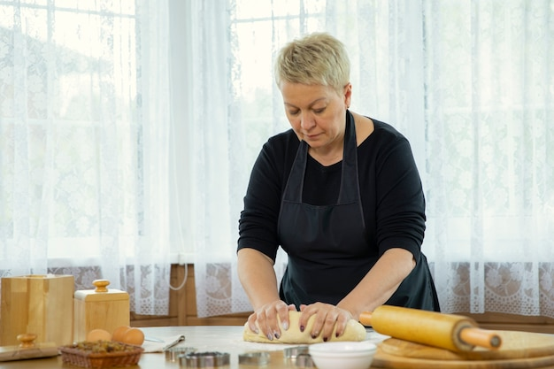 Housewife in black apron kneads raw dough with her hands on the table with flour