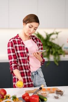 Домохозяйка в клетчатой рубашке проверяет электронную почту или пишет текстовые сообщения со своего смартфона во время готовки. молодой