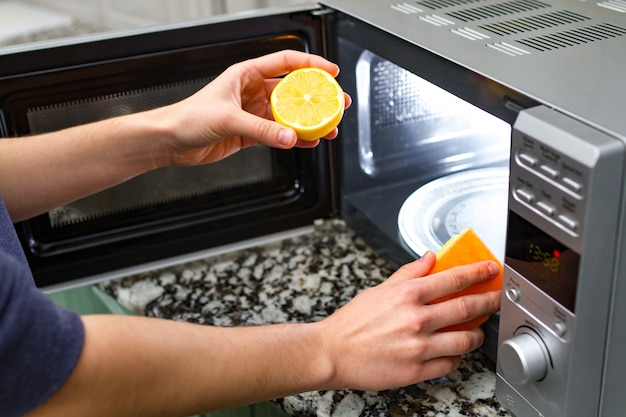 Housewife cleaning microwave oven using lemon