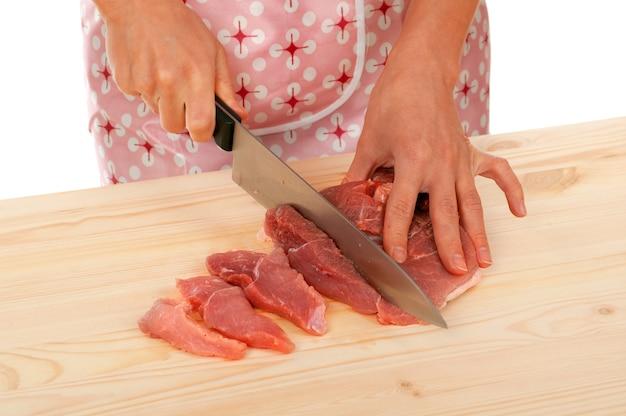 木の板に牛肉を切る主婦。スタジオ、白い背景。