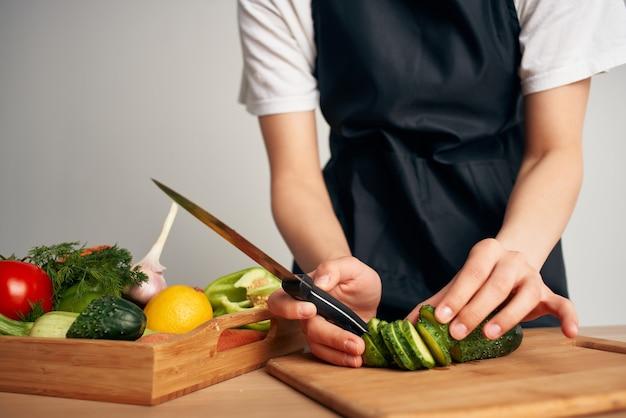 サラダの材料を食べて健康的な野菜を切る主婦