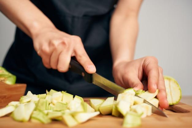 キッチンでビタミンを食べて健康的な野菜を切る主婦