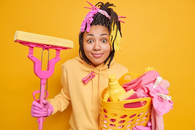 Housewife dressed in casual sweatshirt protective rubber gloves holds basket full of laundry with detergents and mop involved in domestic work isolated on yellow